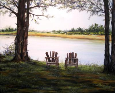 Two empty Adirondack chairs by the river